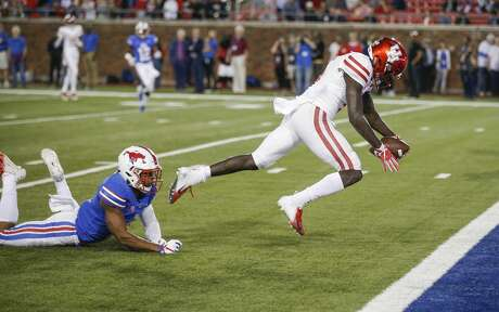 Houston wide receiver Marquez Stevenson (5) runs a pass in for a touchdown as SMU defensive back Rodney Clemons (8) defends during the first half of an NCAA college football game, Saturday, Nov. 3, 2018, in Dallas. (AP Photo/Brandon Wade)