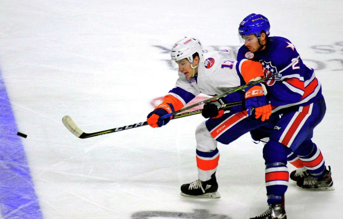 The Sound Tigers' Michael Dal Colle holds off a Rochester defender to make a pass in a game on Oct. 13 at the Webster Bank Arena in Bridgeport.