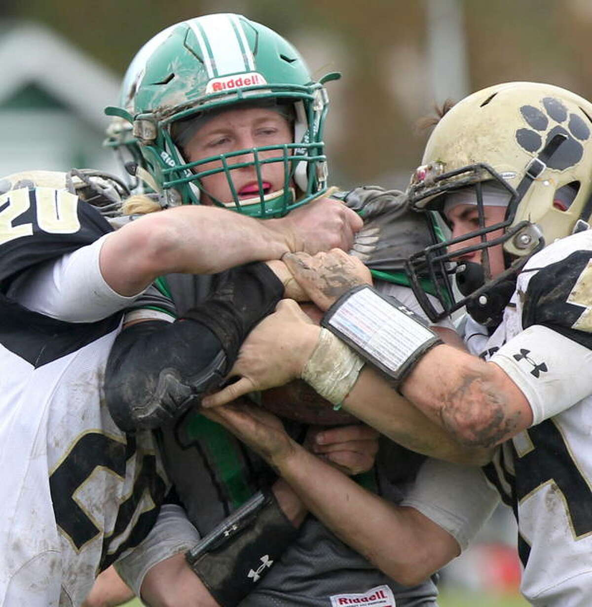 Carrollton quarterback Hunter Flowers hangs onto the ball as two Camp Point Central players try to strip it away in the second round of the IHSA Class 1A playoffs Saturday in Carrollton.