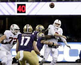 Stanford quarterback K.J. Costello, right, is pressured by the Washington defense but gets a pass off during the first half of an NCAA college football game Saturday, Nov. 3, 2018, in Seattle. (AP Photo/Elaine Thompson)