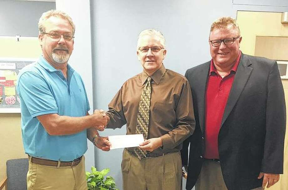 "Jacksonville Mayor Andy Ezard (right) and Kelly Hall (left), the city's Community Development and Recreational Facilities director, present Jacksonville School District 117 Superintendent Steve Ptacek a check for $17,281 to help fund a handrails and steps project at the JHS Bowl. The money was allocated from the downtown tax increment financing district. The project is a ""great addition to an awesome venue that will help many people with access,"" Ezard said. Photo: Photo Provided"