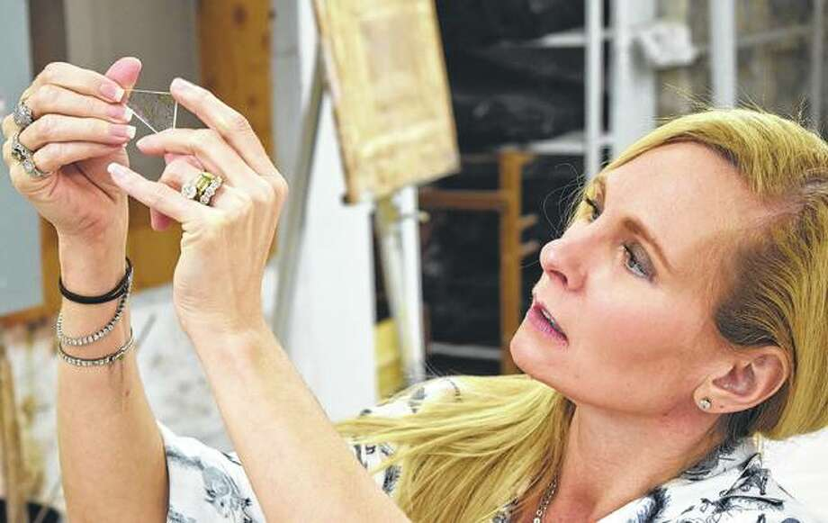 Nicole Ryan-Johnson of Naples, Florida inspects a piece of glass before making jewelry Saturday during the Fused Glass Jewelry making class at the David Strawn Art Gallery by Rosalinda Post-Lucas. Photo: Samantha McDaniel-Ogletree   Journal-Courier