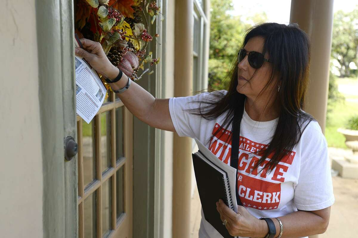 Rhonda Lomonte leaves information on a door while campaigning for the Jefferson County Republican Party on Saturday. Photo taken Saturday 11/3/18 Ryan Pelham/The Enterprise