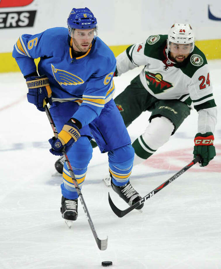 The Blues' Joel Edmundson (left) skates by the Wild's Matt Dumba during the second period Saturday night in St. Louis. Photo: Associated Press