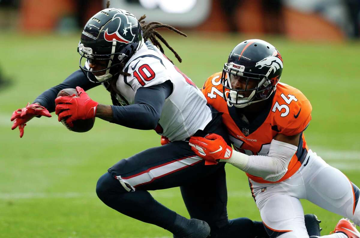 Houston Texans wide receiver DeAndre Hopkins (10) is tackled by Denver Broncos strong safety Will Parks (34) as he makes a first down reception during the first quarter of an NFL football game at Broncos Stadium at Mile High on Sunday, Nov. 4, 2018, in Denver.