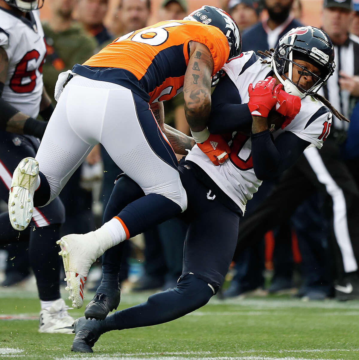 Houston Texans wide receiver DeAndre Hopkins (10) is tackled by Denver Broncos linebacker Shane Ray (56) as Hopkins fights for a first down during the third quarter of an NFL football game at Broncos Stadium at Mile High on Sunday, Nov. 4, 2018, in Denver.