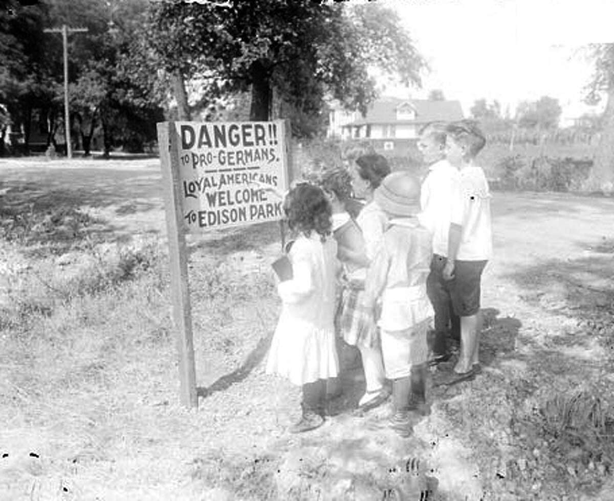 Group portrait of a group of children standing in front of an anti-German sign posted in the Edison Park community area of Chicago, Illinois in 1917.