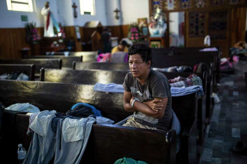 A Central American migrant wakes up inside a church that opened its doors to members of a caravan who splintered off the main group in order to reach the capital faster, in Puebla, Mexico, Sunday, Nov. 4, 2018. Thousands of wary Central American migrants resumed their push toward the United States on Sunday, a day after arguments over the path ahead saw some travelers splinter away from the main caravan, which is entering a treacherous part of its journey through Mexico. (AP Photo/Rodrigo Abd)