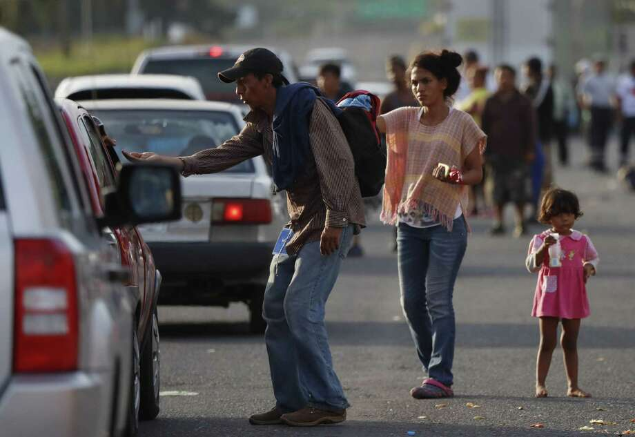 Central American migrants traveling with a U.S.-bound caravan beg for money from passing cars in Cordoba, Veracruz state, Mexico, Sunday, Nov. 4, 2018. On Sunday, the bulk of the caravan streamed into the colonial city of Cordoba, in Veracruz's sugar belt. (AP Photo/Marco Ugarte) Photo: Marco Ugarte, STF / Associated Press / Copyright 2018 The Associated Press. All rights reserved.