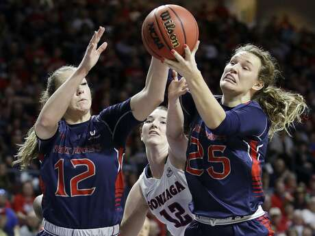 Saint Mary's Sydney Raggio, left, and Megan McKay, right, go for a rebound against Gonzaga's center Emma Wolfram (12) in the first half of an NCAA college basketball game during the championship of the West Coast Conference tournament, Tuesday, March 7, 2017, in Las Vegas. (AP Photo/John Locher)