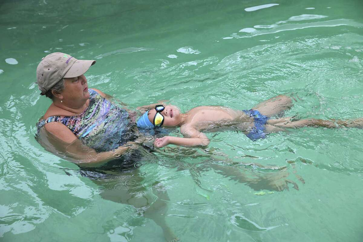 Diana Perry works with 3-year-old Logan Durham during swimming lessons at Perry's home in October. Perry, a retired nurse practitioner and experienced swimmer, teaches special-needs kids.