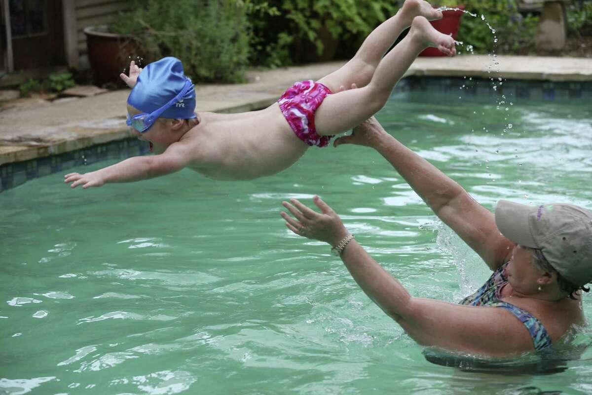 Diana Perry tosses three-year-old Teddy Berios during swimming lessons at her house, Tuesday, Oct. 23, 2018. Perry is the founder of Good Swim, a program that teaches special needs children. She has been a swimming instructor for 30 years.