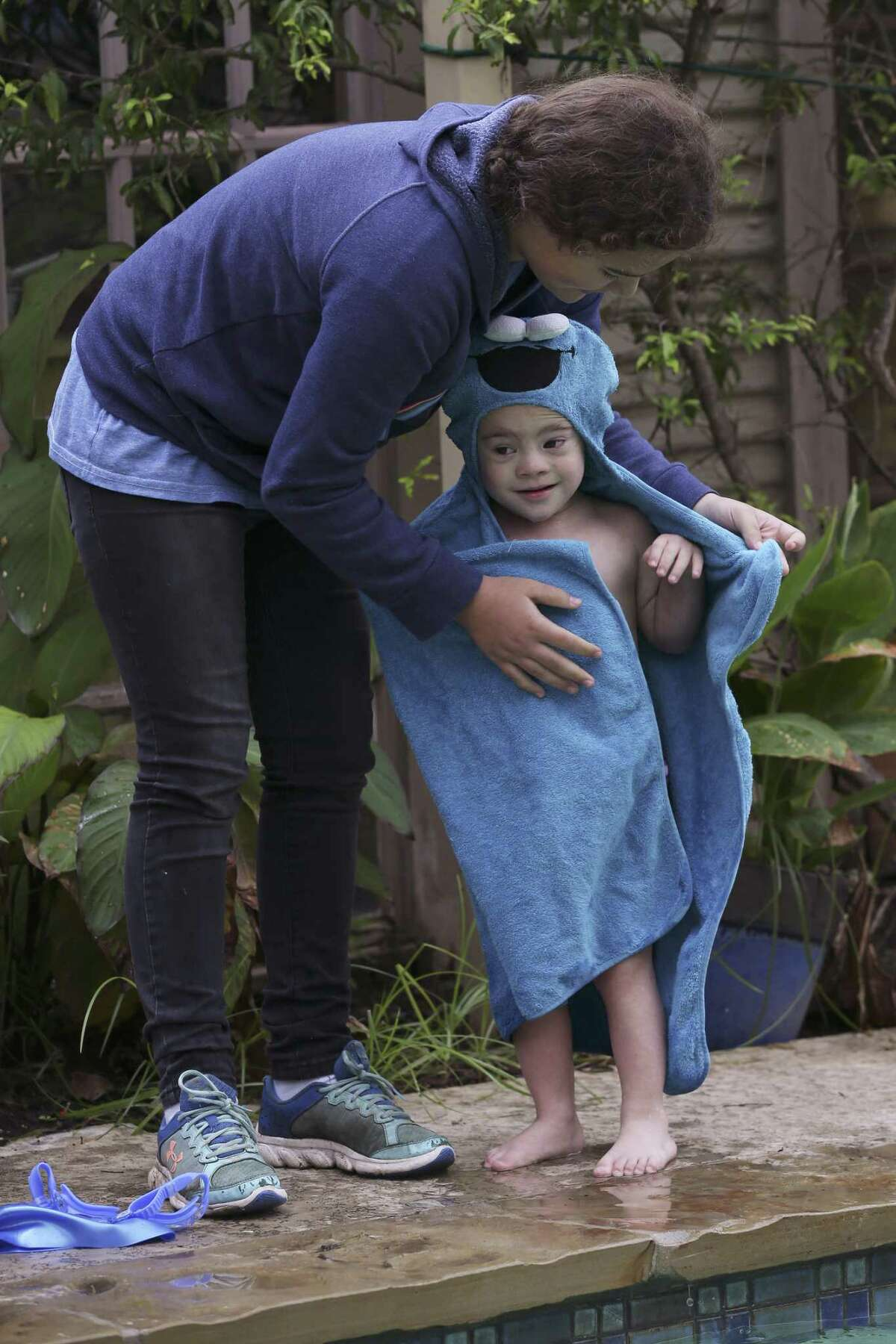Ava Berios, 12, helps her brother, Teddy, 3, dry off after swimming lessons with Diana Perry on Oct. 23. The special-needs tyke has taken to the water like the proverbial fish, thanks to Perry's individualized instruction.