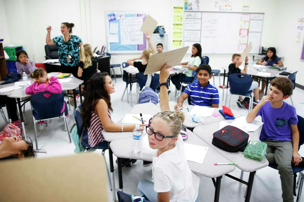 Eastside Intermediate School fourth grader Aubrie Brown, 9, center, holds up an answer to a math problem Monday Sept. 17, 2018 in Cleveland. Enrollment at Cleveland ISD has nearly doubled since 2014 from 3,800 to 6,500 students, straining the district and schools.
