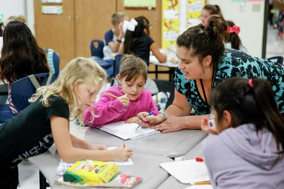 Eastside Intermediate School teacher Brittany Marek, right, helps fourth grader Stephanie Lawson, 9, with a math problem Monday Sept. 17, 2018 in Cleveland. Enrollment at Cleveland ISD has nearly doubled since 2014 from 3,800 to 6,500 students, straining the district and schools.