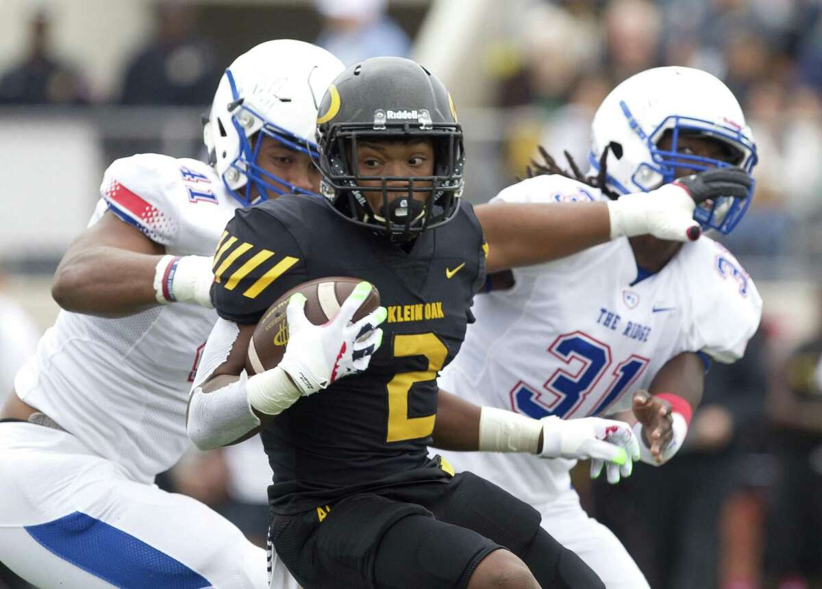 Klein Oak running back Kendal Taylor (2) is brought down by Oak Ridge defensive lineman Darius Richmond (41) and outside linebacker Jordan McDavis (31) during the first quarter of a District 15-6A high school football game at Klein Memorial Stadium, Saturday, Oct. 20, 2018, in Spring.