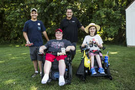 Jiffy Lube International, Inc. president Patrick Southwick, third from left, poses with winners and their handmade cars they used in a derby race he helped judge during the Muscular Dystrophy Association's annual MDA Summer Camp in Chestertown, Md.