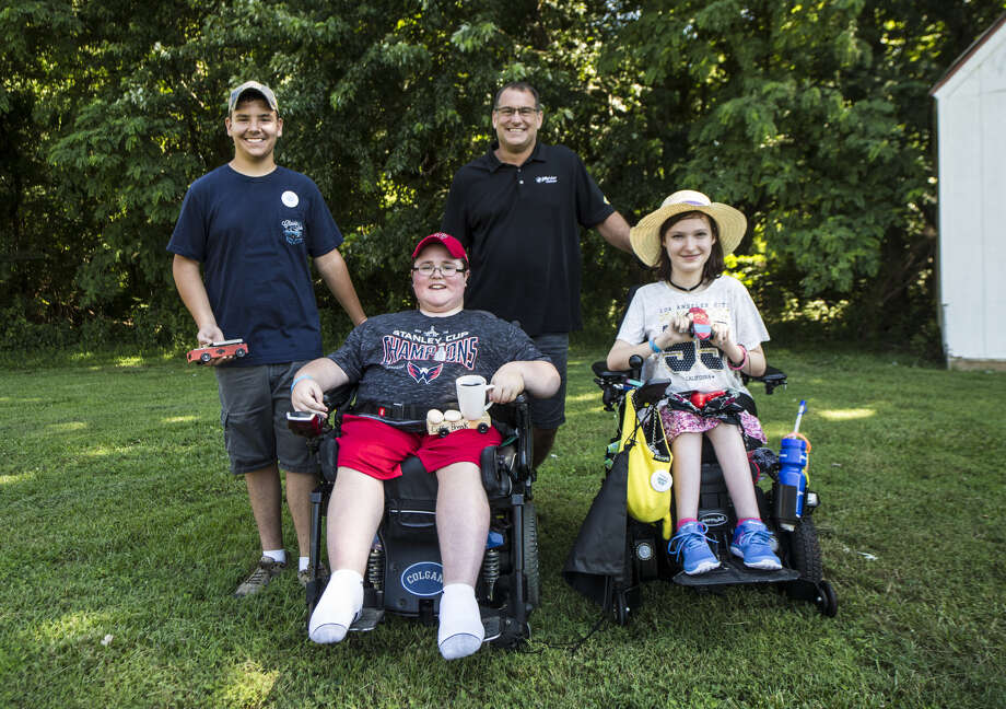Jiffy Lube International, Inc. president Patrick Southwick, third from left, poses with winners and their handmade cars they used in a derby race he helped judge during the Muscular Dystrophy Association's annual MDA Summer Camp in Chestertown, Md. Photo: Courtesy Of Jiffy Lube