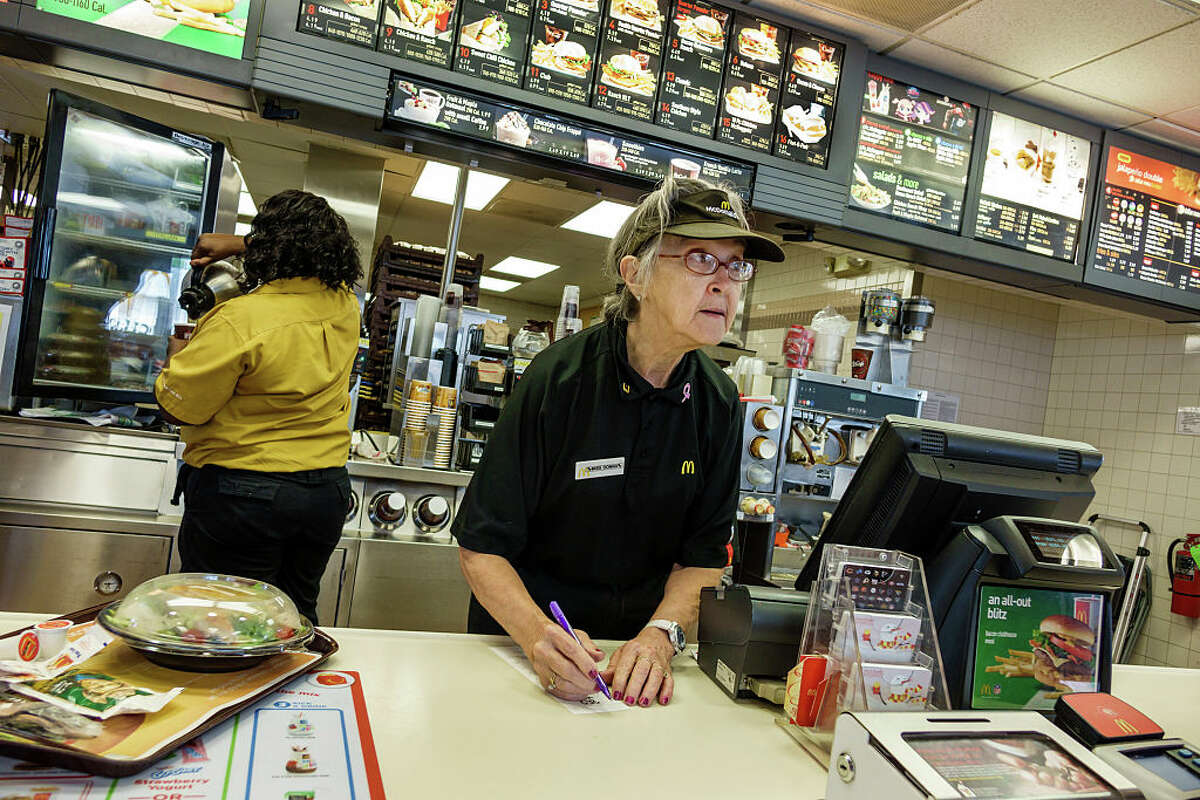 A senior woman working in a McDonald's restaurant. Seniors are replacing teenage employees at many fast food establishments.