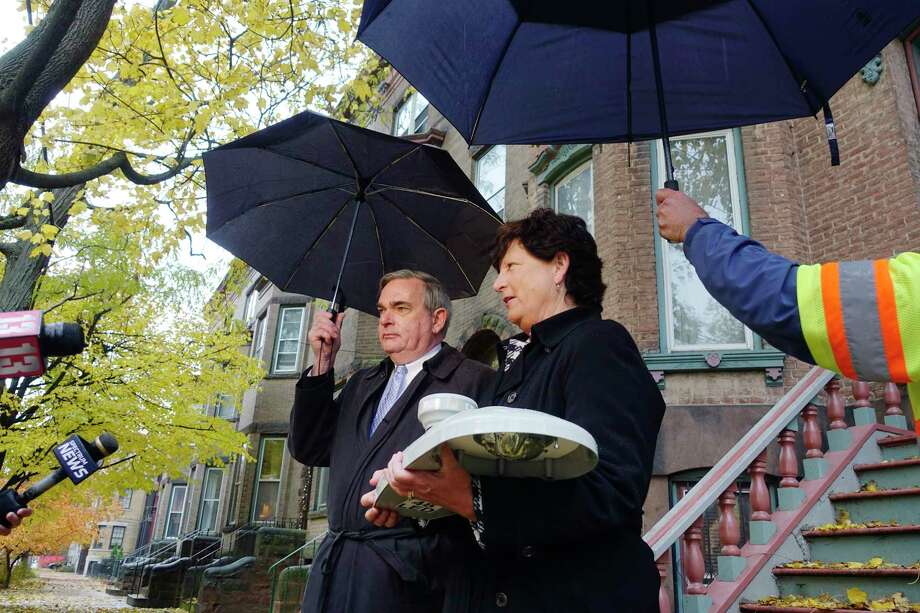 Schenectady Mayor Gary McCarthy, left, and Laurie Poltynski, National Grid's eastern New York regional executive, talk to members of the media about the new advanced street lighting technology being installed in the city on Monday, Nov. 5, 2018, in Schenectady, N.Y. Poltynski is holding one of the LED street lights.  (Paul Buckowski/Times Union) Photo: Paul Buckowski, Albany Times Union / (Paul Buckowski/Times Union)