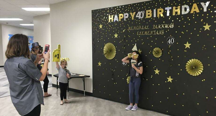 Visitors to Memorial Parkway Elementary could grab a birthday hat and super-sized glasses to have their photos taken in front of the birthday wall. Photo: Karen Zurawski / Karen Zurawski