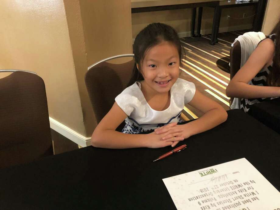 "Yutia Li smiles as she waits to autograph copies of the book that contains her published story ""Sweet Stunning Skyscraper"" at the iWrite Literacy Organization luncheon Saturday, Oct. 27, at the Hyatt Regency in downtown Houston. The event recognized 78 student authors and illustrators. Photo: Tracy Maness"
