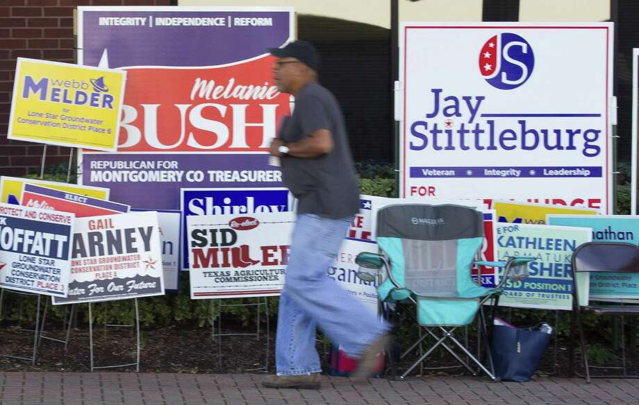 A man walks past a plethora of political candidate signs in front of early voting location at the Lee G. Alworth Building, Thursday, Nov. 1, 2018, in Conroe.>>>See some of the most unusual polling places in Houston.... Photo: Jason Fochtman, Houston Chronicle / Staff Photographer / © 2018 Houston Chronicle