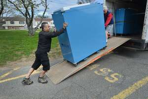 Angelo Greco and Rich Bartlett roll a cabinet from a truck containing ballots, tabulators and voting items into the polling place at Nathan Hale School in Norwalk. Conn. The polls will be open on Tuesday, Nov. 6, 2018, from 6 a.m. to 8 p.m.