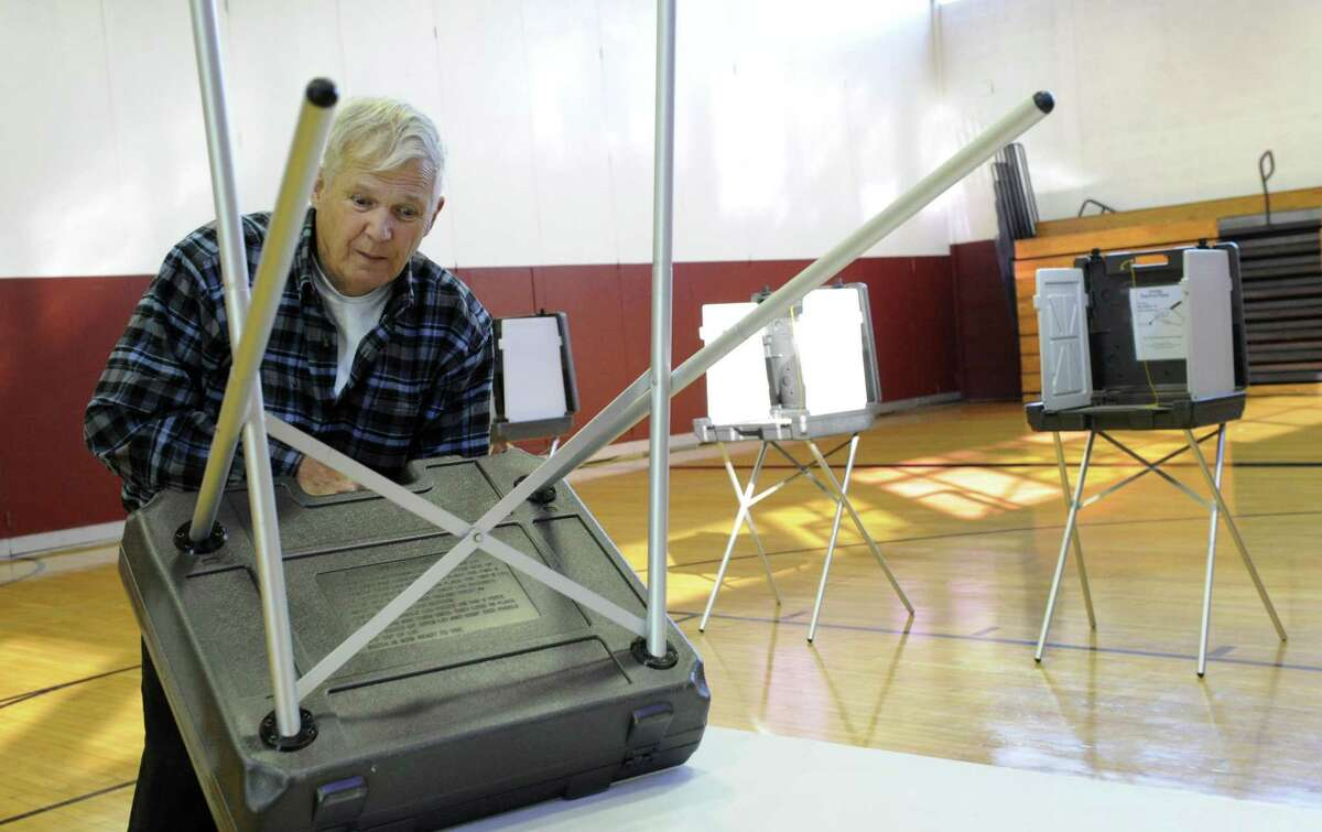 A town worker sets up voting tables at the Bethel Municipal Center polling place in Bethel, Conn. Polls will be open on Tuesday, Nov. 6, 2018, from 6 a.m. to 8 p.m.