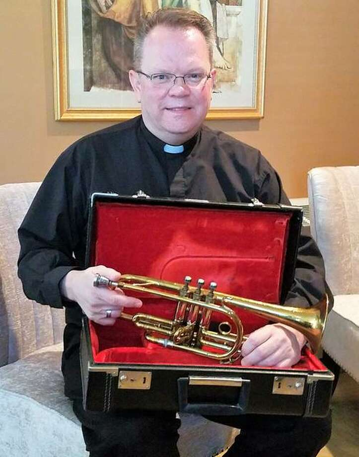 Fr. Jeffrey Goeckner, the pastor of St. Boniface in Edwardsville, pictured with the cornet of former student St. Kenneth Scheibal. Scheibal's niece Joan Gillham recently donated the cornet to the parish. Photo: Carol Arnett | The Intelligencer