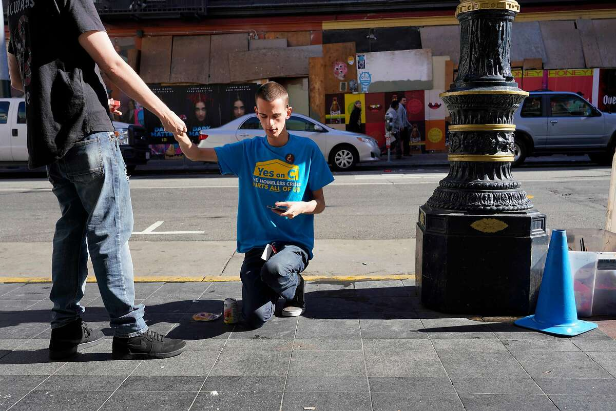Anubis Daugherty (right) gets help from his brother Robert Daugherty (left) as he fills a cigarette case as he heads to work to work at the Yes on C phone bank on Monday, November 5, 2018 in San Francisco, Calif.