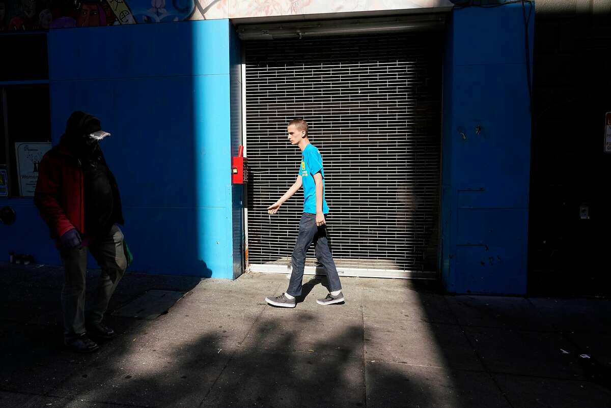 Anubis Daugherty walks along Turk Street on his way to work at the Yes on C phone bank on Monday, November 5, 2018 in San Francisco, Calif.