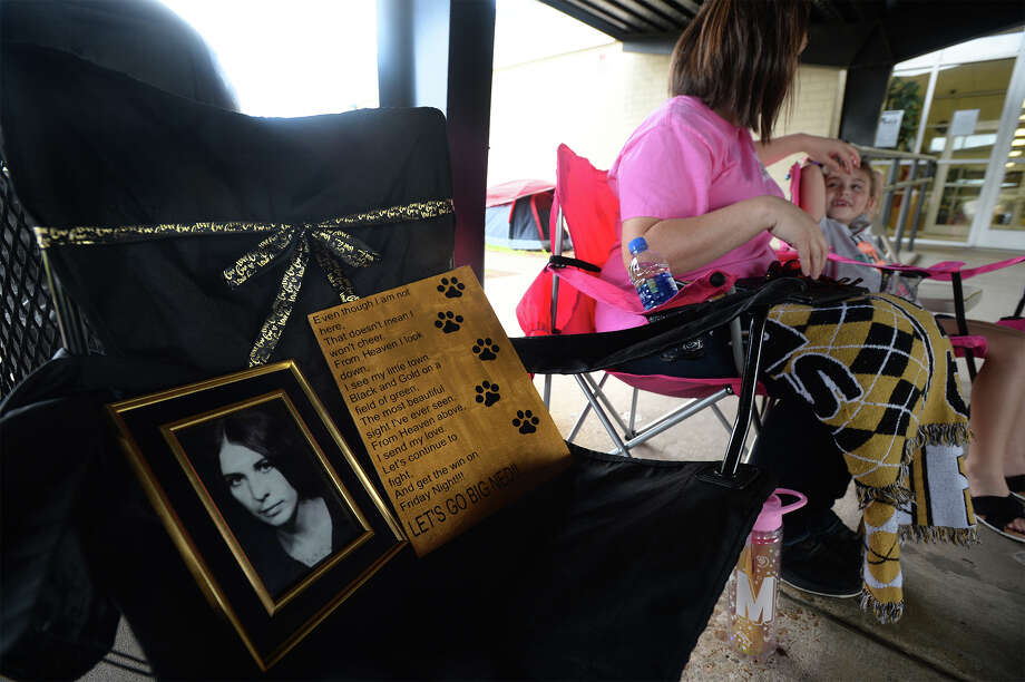 Pam Coleman's picture is displayed in a black folding chair near the front of the line to purchase Mid-County Madness football tickets at Nederland High School on Monday. Coleman, who died from cancer in August was known for being at the front of the line for the past 10 years. Coleman's daughter, Summer Molina and granddaughter Makayla Molina, 6, are pictured. Molina began camping Sunday around 10:15 for the tickets which go on sale today.  Photo taken Monday, 11/5/18 Photo: Guiseppe Barranco/The Enterprise / Guiseppe Barranco ?