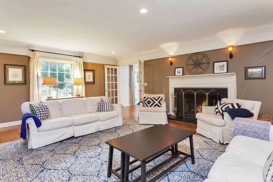 The formal living room at 16 Linda Lane in Darien features a white trimmed fireplace with a brick surround, oversized windows and French doors that open to a sunroom. Photo: Halstead Connecticut / ONLINE_CHECK
