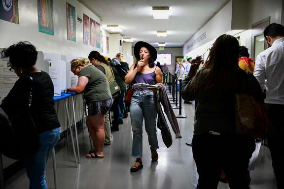 Allison Cuozzo walks through the Registrar of Voters office before casting her vote in Oakland, California, on Monday, Nov. 5, 2018.