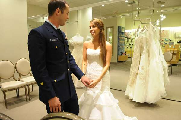 USO Coast Guardsman of the Year, Sam Peikert, stationed in Opa Locka, Fla., and his bride-to-be, Jackie Fairchild, of Houston, Texas, shop for wedding gowns at the David's Bridal store on Veterans Day, Monday, Nov. 11, 2013, in New York, after his surprise proposal on television with recording artist Jason Derulo. David's Bridal is showing its support for Veterans Day by offering a 20 percent discount to all service members and veterans through Nov. 15.