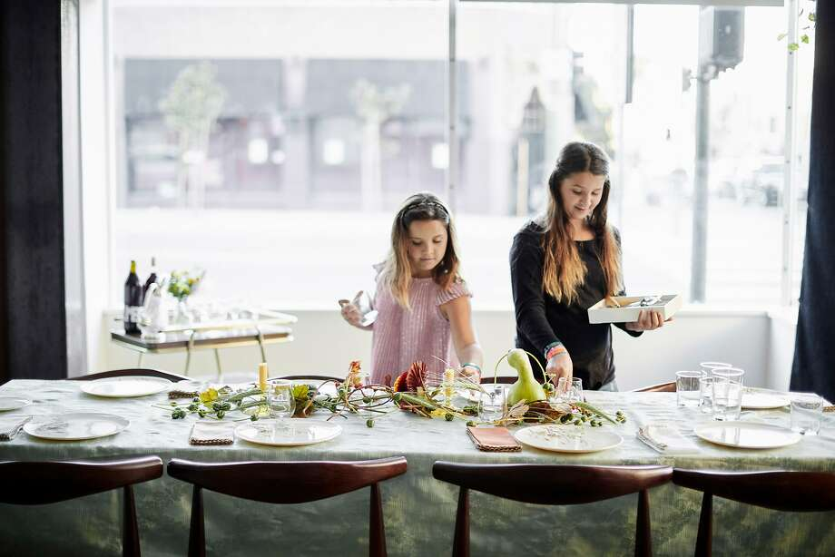 Jason Fox's daughters, Emma and Lily, set the Friendsgiving table. Photo: John Lee / Special To The Chronicle