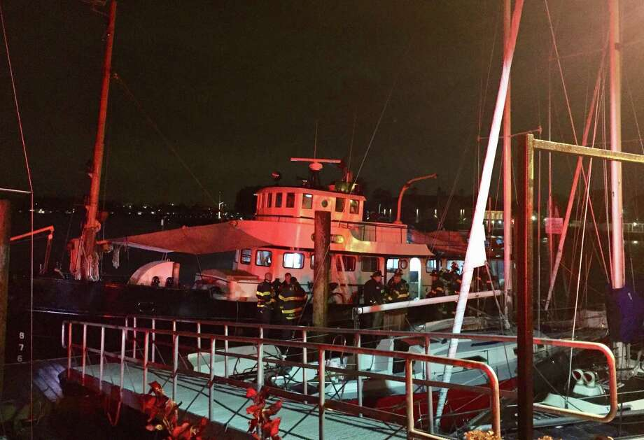 Firefighters gather on The General, a retired U.S. Army tugboat-turned-yacht, after an electrical fire started in the engine compartment below deck on Monday, Nov. 5, 2018. Photo: Thane Grauel / Hearst Connecticut Media