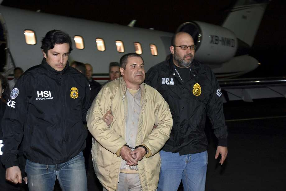 """FILE - In this Jan. 19, 2017 file photo provided U.S. law enforcement, authorities escort Joaquin """"El Chapo"""" Guzman, center, from a plane to a waiting caravan of SUVs at Long Island MacArthur Airport, in Ronkonkoma, N.Y. Jury selection has begun under tight security at the New York trial of the Mexican drug lord. Potential jurors were quizzed Monday, Nov. 5, 2018, about their attitudes on drug trafficking and how much attention they've paid to news reports about Guzman. (U.S. law enforcement via AP, File) Photo: Associated Press"""