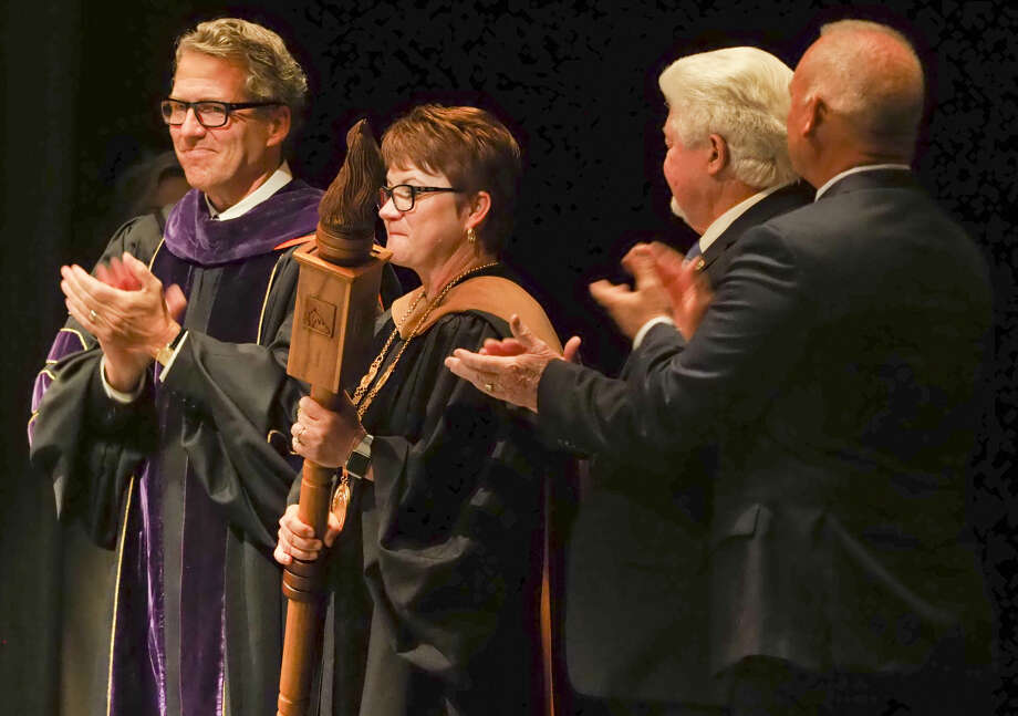 Chancellor James Milliken, The University of Texas System, presents Sandra Woodley, UTPB President, with the Presidential Medallion and the University Mace Monday as her husband, Stan Woodley and father, Jack Green, look on. Photo: Tim Fischer/Reporter-Telegram
