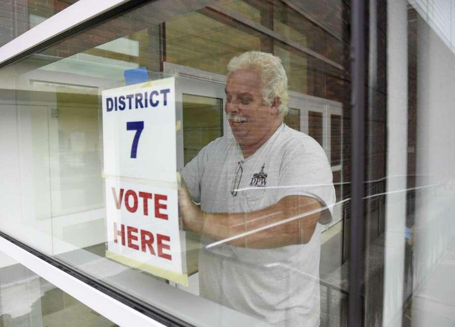 Greenwich Department of Public Works employee Ken Schlosser posts a sign outside the District 7 polling station at Greenwich High School Monday. Photo: Tyler Sizemore / Hearst Connecticut Media / Greenwich Time