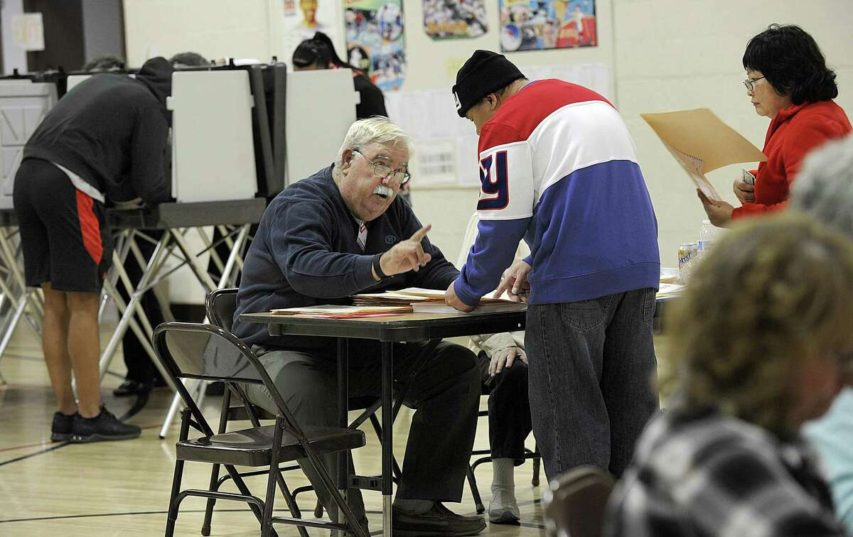 Phil Curran, a ballet clerk at the Park Avenue School polling place in Danbury, explains procedure to a resident on Election Day in 2016.