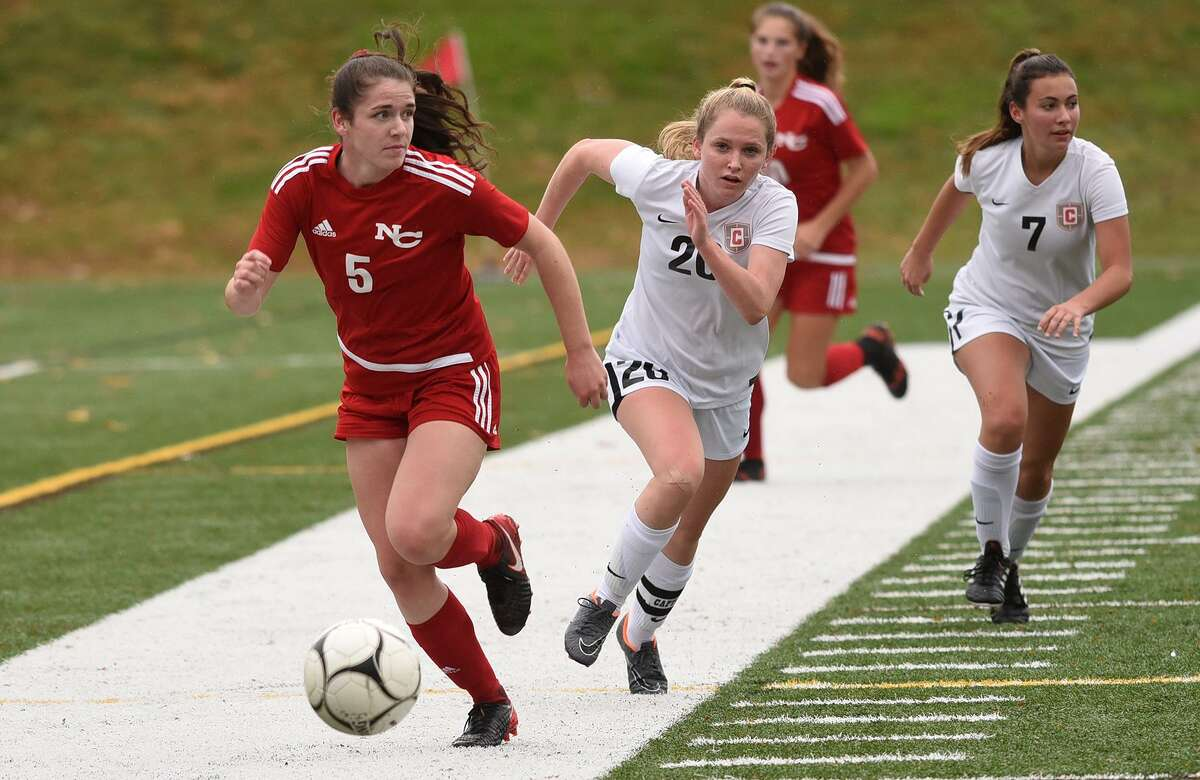 New Canaan's Elizabeth St. George is pursued by Conard's Lauren Massaro during Monday's game in New Canaan.