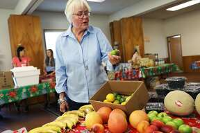 Sheryl Boucher, is 72, a retired preschool teacher and operator, inspects a lime as she receives food from the Marin County Food Bank at Holy Innocents Episcopal Church in Corte Madera, Calif., on Thursday, September 20, 2018.