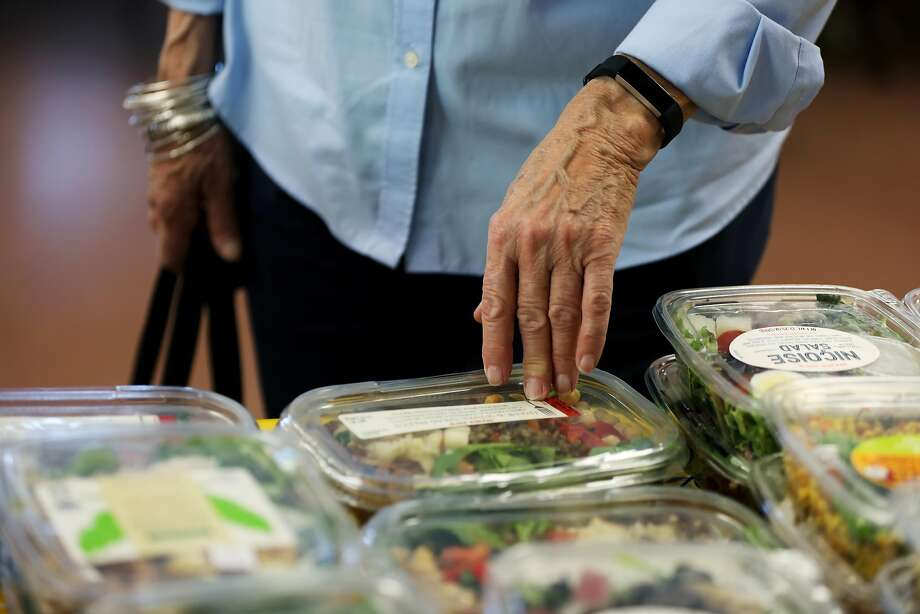 Retired preschool director Sheryl Boucher, 72, looks at packaged salads available at the San Francisco-Marin Food Bank pantry at Holy Innocents Episcopal Church in Corte Madera. Photo: Yalonda M. James / The Chronicle
