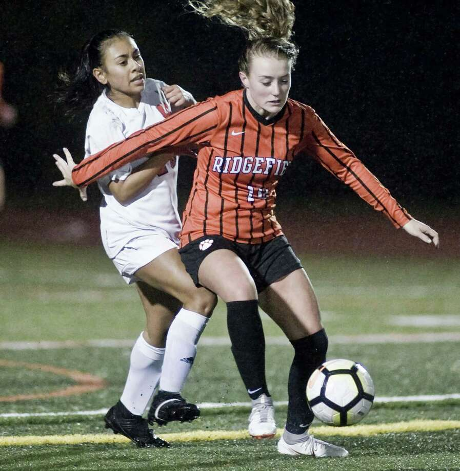 Manchester High School's Analise Ortiz tries to get around Ridgefield High School's Megan Klosowski in the Class LL girls soccer game at Ridgefield. Monday, Nov. 5, 2018 Photo: Scott Mullin / For Hearst Connecticut Media / The News-Times Freelance