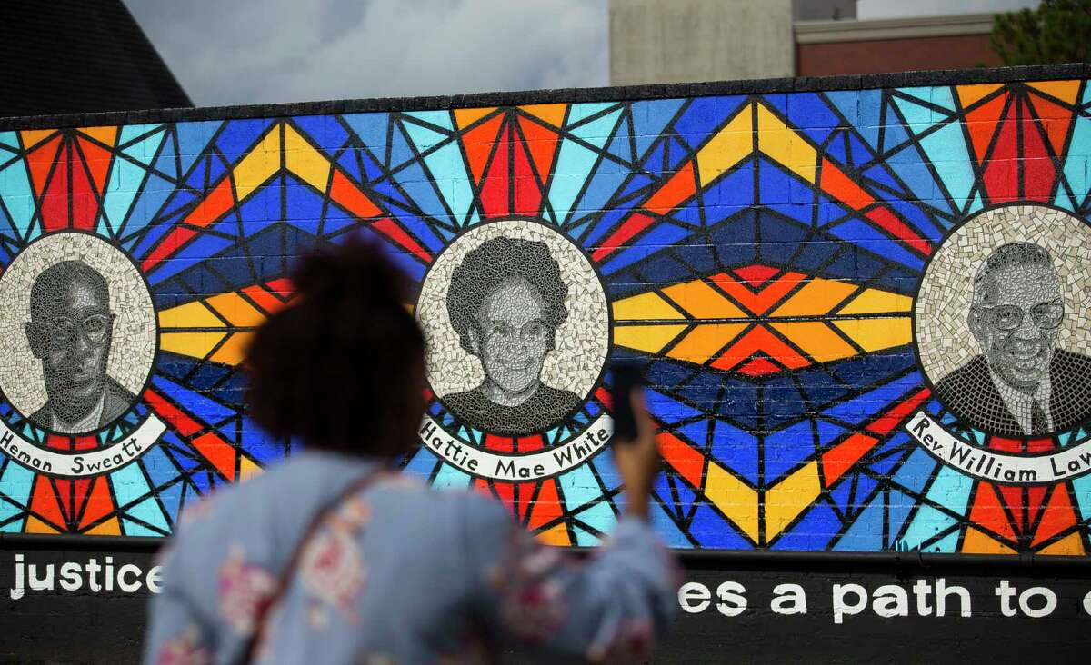 A woman photographs the new mural The Sacred Struggles / Vibrant Justice Mural along the Columbia Tap trail behind the Pilgrim Congregational United Church of Christ, Monday, Nov. 5, 2018 in Houston. The mural pays tribute to eight of Houston's African American civil rights leaders.