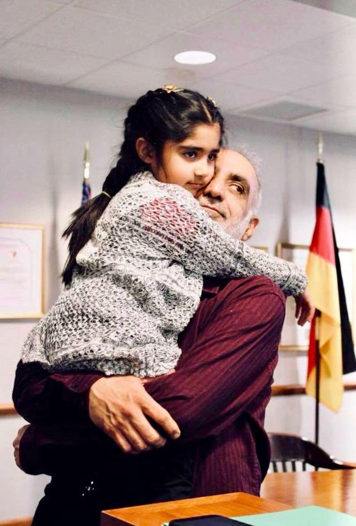 Malik Naveed bin Rehman holds his daughter, Roniya.