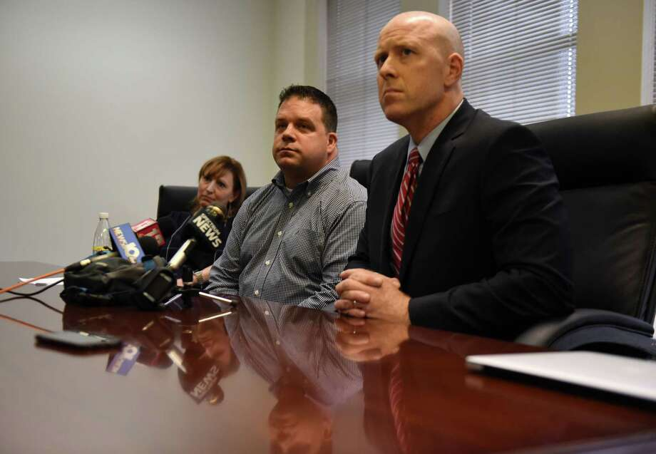 Darren Ayotte, center, speaks during a news conference with his attorney, Lee Kindlon, right, on Monday, Nov. 5, 2018, at Lindon's legal offices in Albany, N.Y. Kindlon raised questions about how prosecutors handled the case against Dominick Comitale, the Troy cop accused of hitting Ayotte on a Little League field and confronting a woman in an apparent road rage case. (Will Waldron/Times Union) Photo: Will Waldron / 20045386A