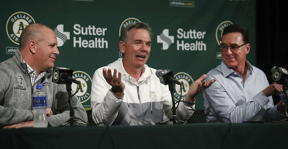 FILE - In this Oct. 5, 2018 file photo, Oakland Athletics' Executive VP of Baseball Operations Billy Beane, center, gestures beside General Manager David Forst, left, and Manager Bob Melvin during a media conference in Oakland, Calif. Manager Bob Melvin has received a long-term contract extension from the Oakland Athletics, who also reached new deals with executive vice president of baseball operations Billy Beane and general manager David Forst. The club announced the extensions Monday, Oct. 29, 2018. Under Melvin's guidance, a young, slugging Oakland club went 97-65 and lost the wild-card game 7-2 to the New York Yankees. (AP Photo/Ben Margot, File)